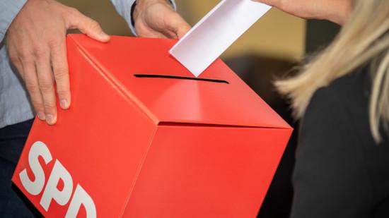 Eine Frau steckt einen Wahlzettel in eine Wahlurne